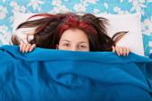 Young girl hiding behind a blanket on her bed — Foto de Stock
