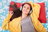 Jong meisje luisteren muziek op haar bed — Stockfoto