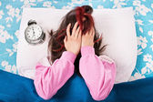 Young girl annoyed by the alarm clock — Stock Photo