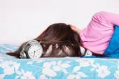 Young girl sleeping while the clock is ringing — Foto Stock