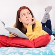 Young girl dream-reading on her bed — Stock Photo #68875917