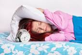 Young girl in bed covering her ears with a pillow from the alarm — Stock Photo