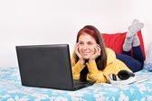 Young girl in her room looking something on her laptop — Stock Photo