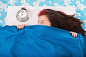 Young girl in bed hiding beneath her blanket from the alarm cloc — Stock Photo