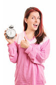 Young girl holding an alarm clock and thumbs up — Stock Photo