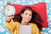 Young girl holding her favorite book and alarm clock — Stock Photo