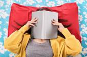 Young girl covering her face with an open book — ストック写真