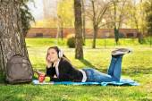 Young girl listening music in the park — Stock Photo