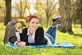 Młoda dziewczyna leżąc na łące trzyma jabłko — Zdjęcie stockowe