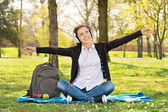 Student in a park with arms outstretched as if she's flying — Stock Photo