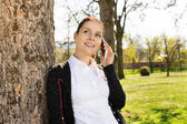 Young girl in park talking on the phone — Stock Photo