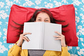 Girl in bed hiding her face behind a book — Foto de Stock