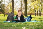 Student lying on a meadow holding a piggy bank — Stock Photo