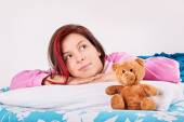 Young girl in her bed, awake with her teddy bear — Stock Photo