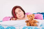 Jong meisje in haar bed, wakker met haar teddybeer — Stockfoto