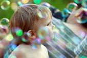 Boy among soap bubbles — Stock Photo