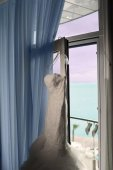 The nice bridal dress is hanging on the window. — Stock Photo