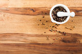 Pepper with mortor on wood table — Stock Photo