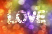 Inscription love with defocused lights on abstract colorful boke — Stock Photo