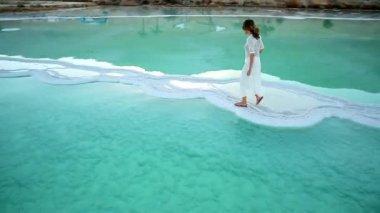 A girl in a white dress crossing the sea девушка в длинном белом платье идет по морской соляной косе — Stock Video