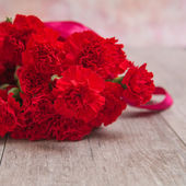 Bouquet of red carnations on wooden background — Stock Photo