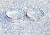 Two wedding rings of white gold on silver glitter sparkle — Stock Photo