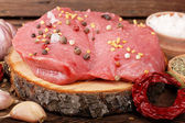 Steak and spices on a wooden surface — Stock Photo