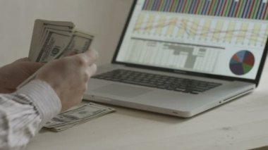 Hands of businessman counting dollar bills in front of a notebook — Stock Video