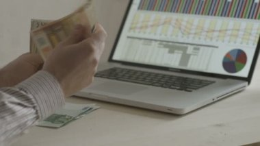 Hands of businessman counting euro bills in front of a notebook — Stock Video