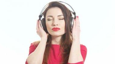 Schöne Frau in rot geschwungen zur Musik in große Kopfhörer mit der Kamera flirten und küssen isoliert auf weißem Hintergrund mittleren Schuss — Stockvideo