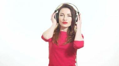 Mulher bonita em vermelho balançando com a música em fones de ouvido grandes, flertando com a câmera e beijando isolado no fundo branco tiro médio — Vídeo stock