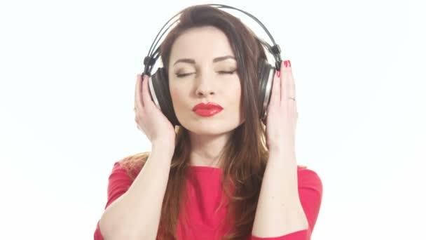 Mujer hermosa en rojo que hace pivotar a la música en auriculares grandes besos y coquetear con la cámara aislada sobre fondo blanco tiro medio — Vídeo de stock