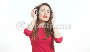 Attractive female in red t-shirt dancing to the music in big headphones notices the camera and send an air kiss isolated on white background medium shot — Stockvideo