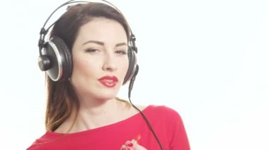 Lovely girl in red listening to the music in big headphones and dancing having fun applying red lipstick isolated on white background close up shot — Stock Video