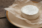 Whole camembert cheese on the white parchment — Stock Photo