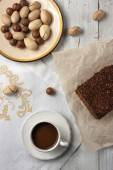 Nuts, chocolate cake and a cup of cofee on the white background — Stock Photo