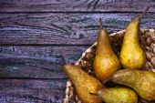 Pears in a braided bowl on a purple background — Stock Photo