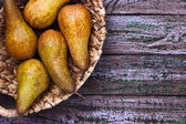 Pears in a braided bowl on a purple background — 图库照片