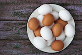 Chicken eggs in a glass and a metall dish on the purple boards — Stock Photo