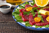 Carpaccio on the white plate on the wooden table — Stock Photo