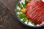 Raw red meat on the plate on the wooden table — Stockfoto