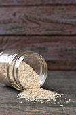 Sesame in the glass jar on the wooden table — Stock Photo