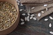 Pumpkin seeds on the rustic wooden table — Stock Photo