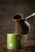 Dark coffee pours from a copper jezve into a green ceramic vinta — Stock Photo