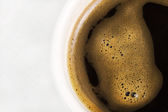 Black coffee in a white cup on a white background — Stock Photo