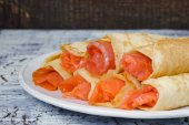 Rolls from pancakes with salmon on the white ceramic plate — Stock Photo