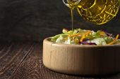Olive oil pours from glass jug into a vegetable salad in a woode — Stock Photo
