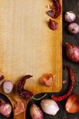 Wooden board with onions, garlic and pepper background — Stock Photo