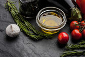 Olive oil with different vegetables and rosemary on the black stone table — Stock Photo