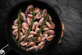 Prawns with sprigs of rosemary in the pan on the black stone table — Stock Photo